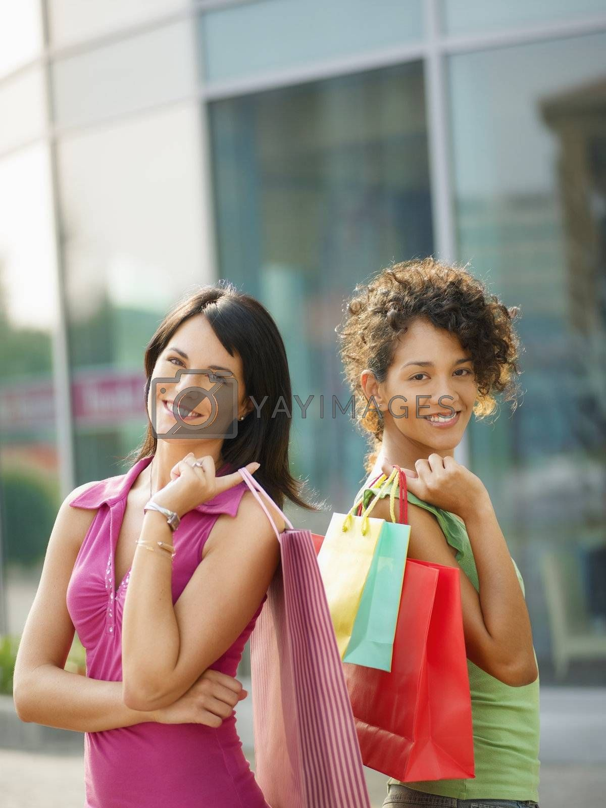 mid adult italian woman and hispanic woman carrying shopping bags out of shopping center. Vertical shape, waist up, copy space