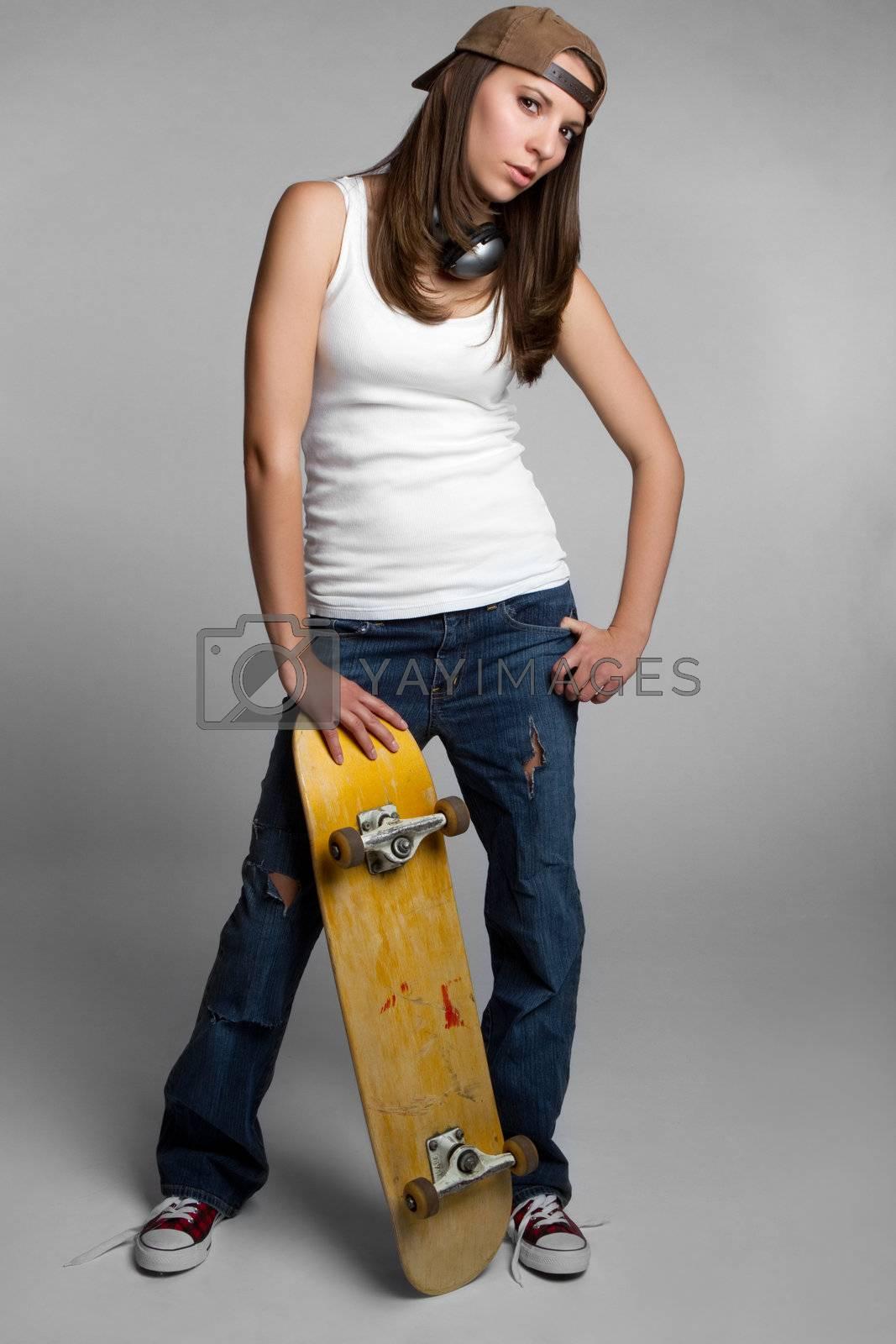 Pretty skater girl holding skateboard