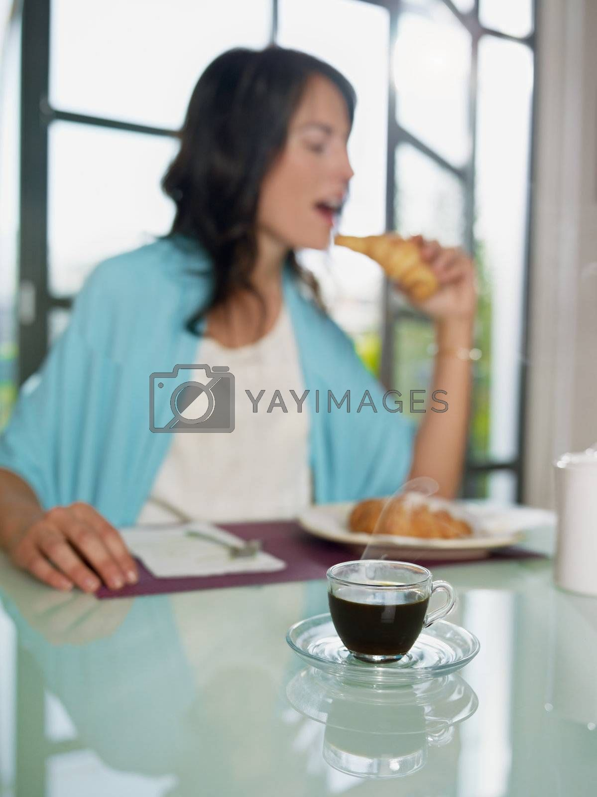 mid adult woman eating croissant at home. Vertical shape, copy space, focus on cup of coffee
