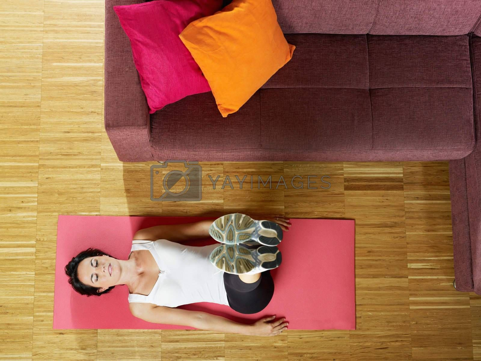 mid adult woman with legs raised training abdominals at home. Horizontal shape, full length, side view, copy space