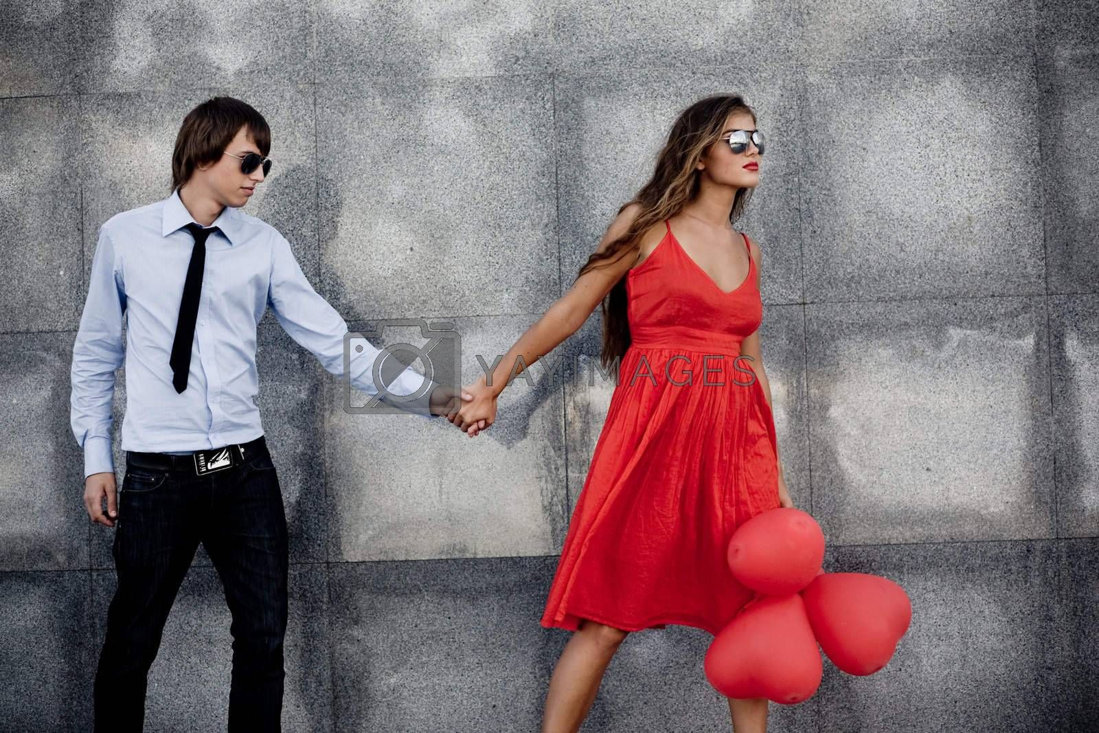 Young couple in sunglasses posing near wall