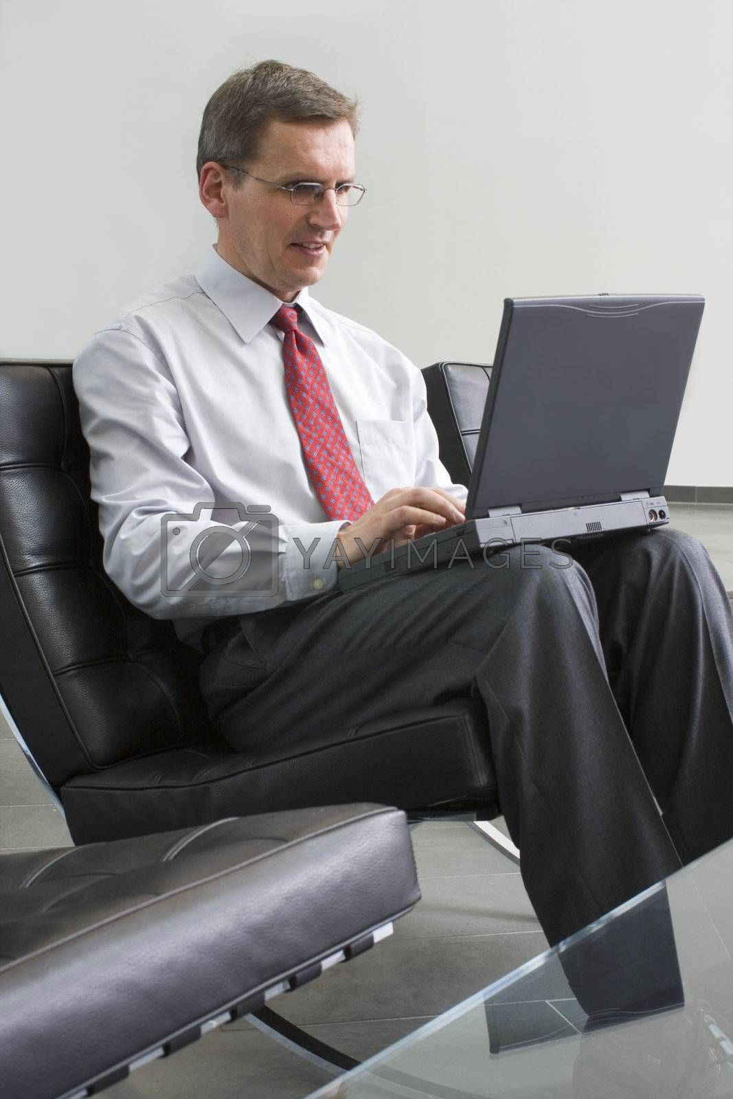 Businessman sitting in a lounge and working with laptop computer