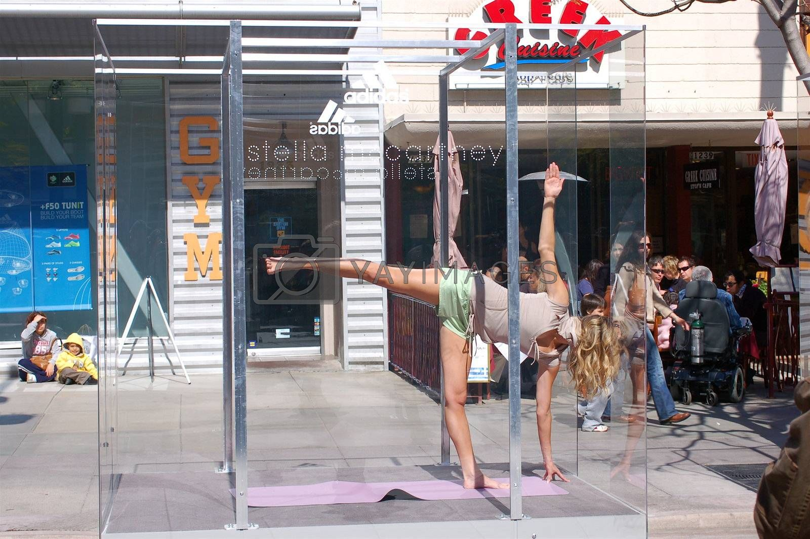 Woman mid yoga pose, wearing shorts and vest, in a glass box on a street in Santa Monica, California