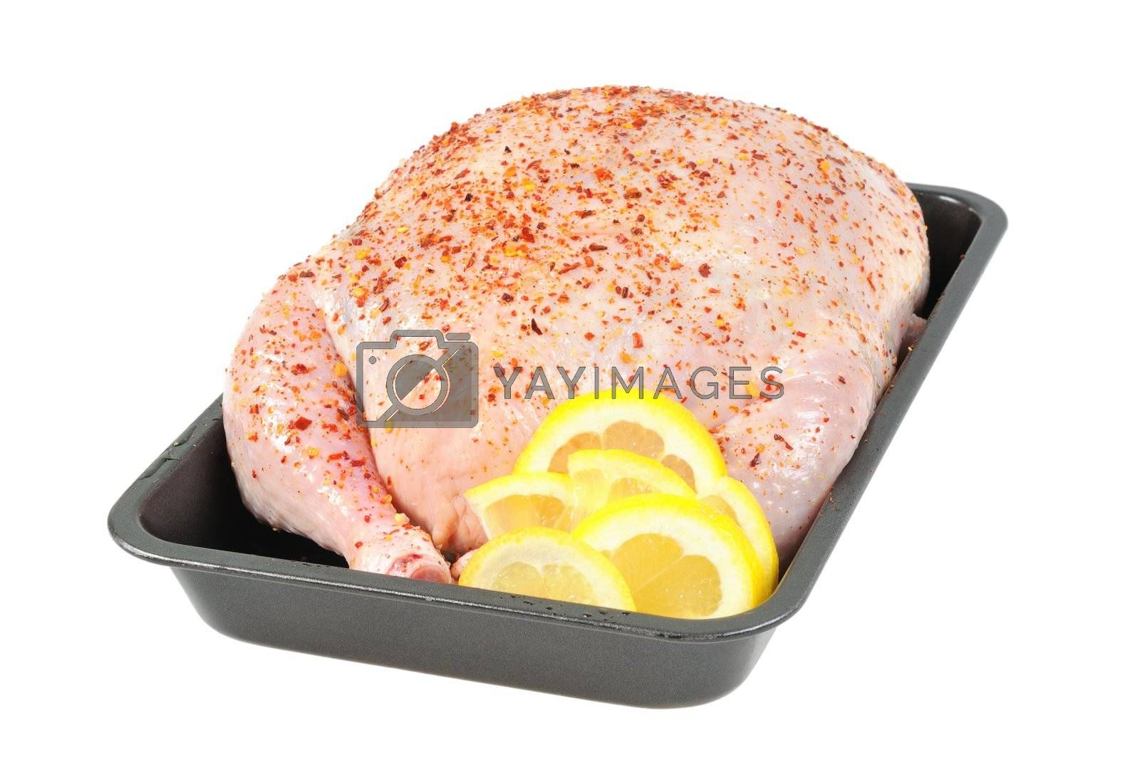 Stuffed chicken  on a baking sheet, decorated with lemon.  Isolated  on white.