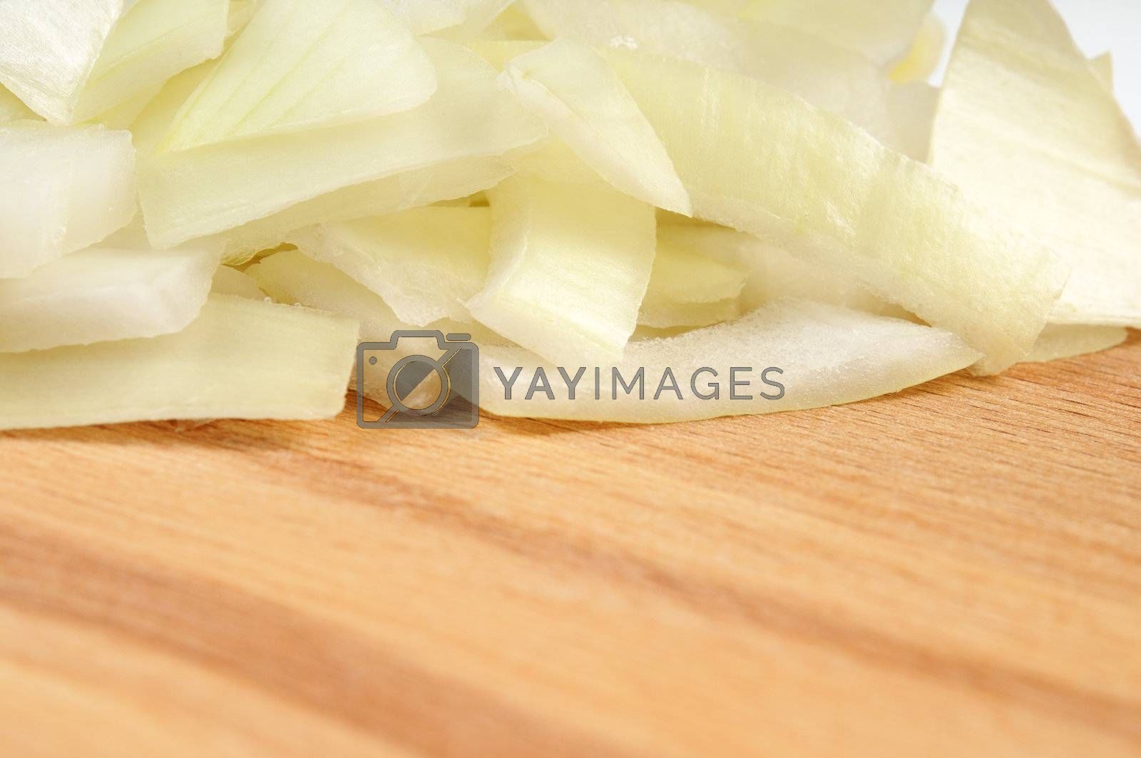 Chopped onions on a wooden board. Isolated on white. Shallow depth of field