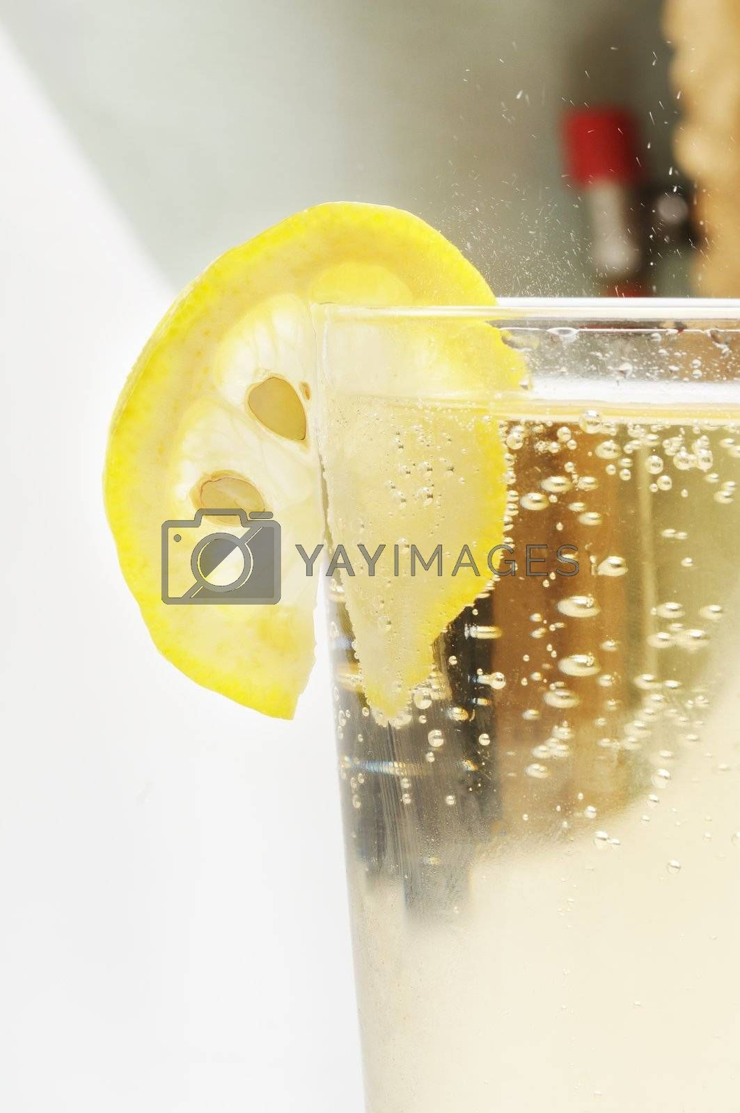 Glass goblet with sparkling lemonade and lemon.