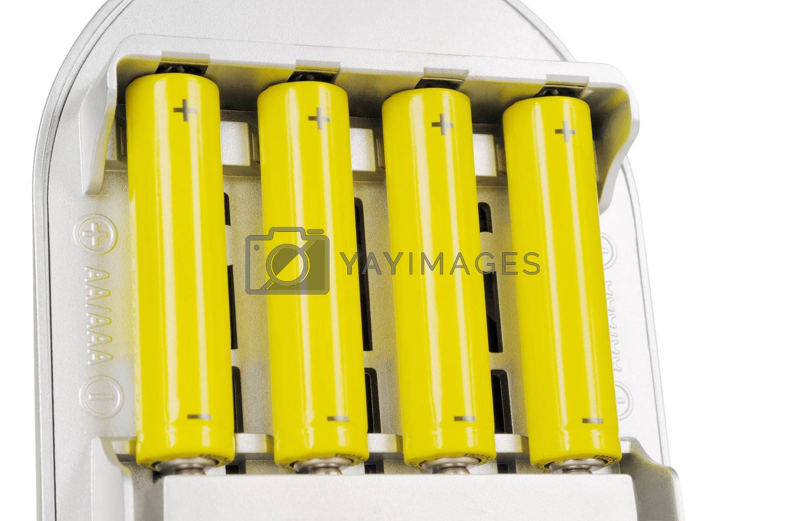 Four batteries in the charger. Isolated on white.