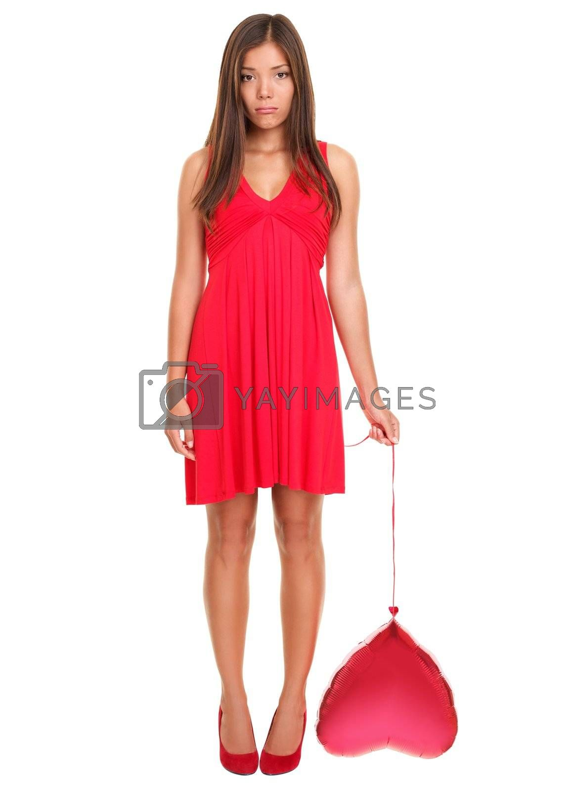Sad woman in love ? funny. Valentines day woman unhappy holding red heart balloon  Beautiful young woman in red dress. Asian / Caucasian female model isolated on white background in full length. Broken heart love concept.