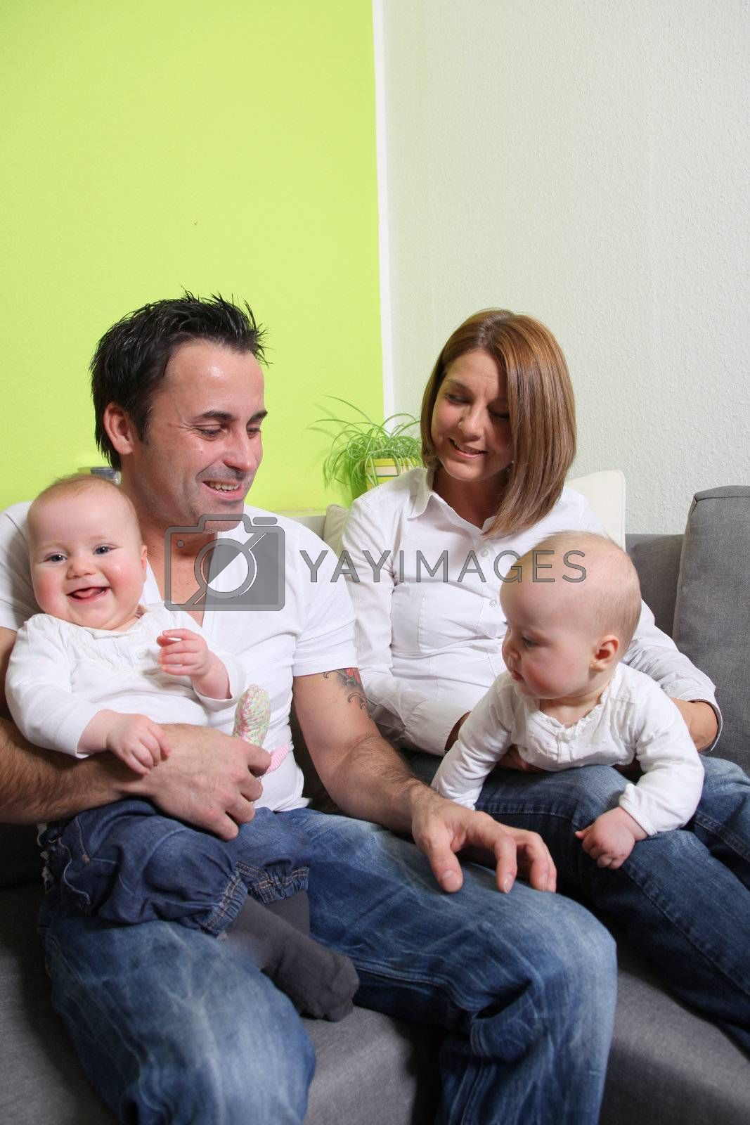 Young families with babies - twins. The parents and the baby laugh friendly and happy.