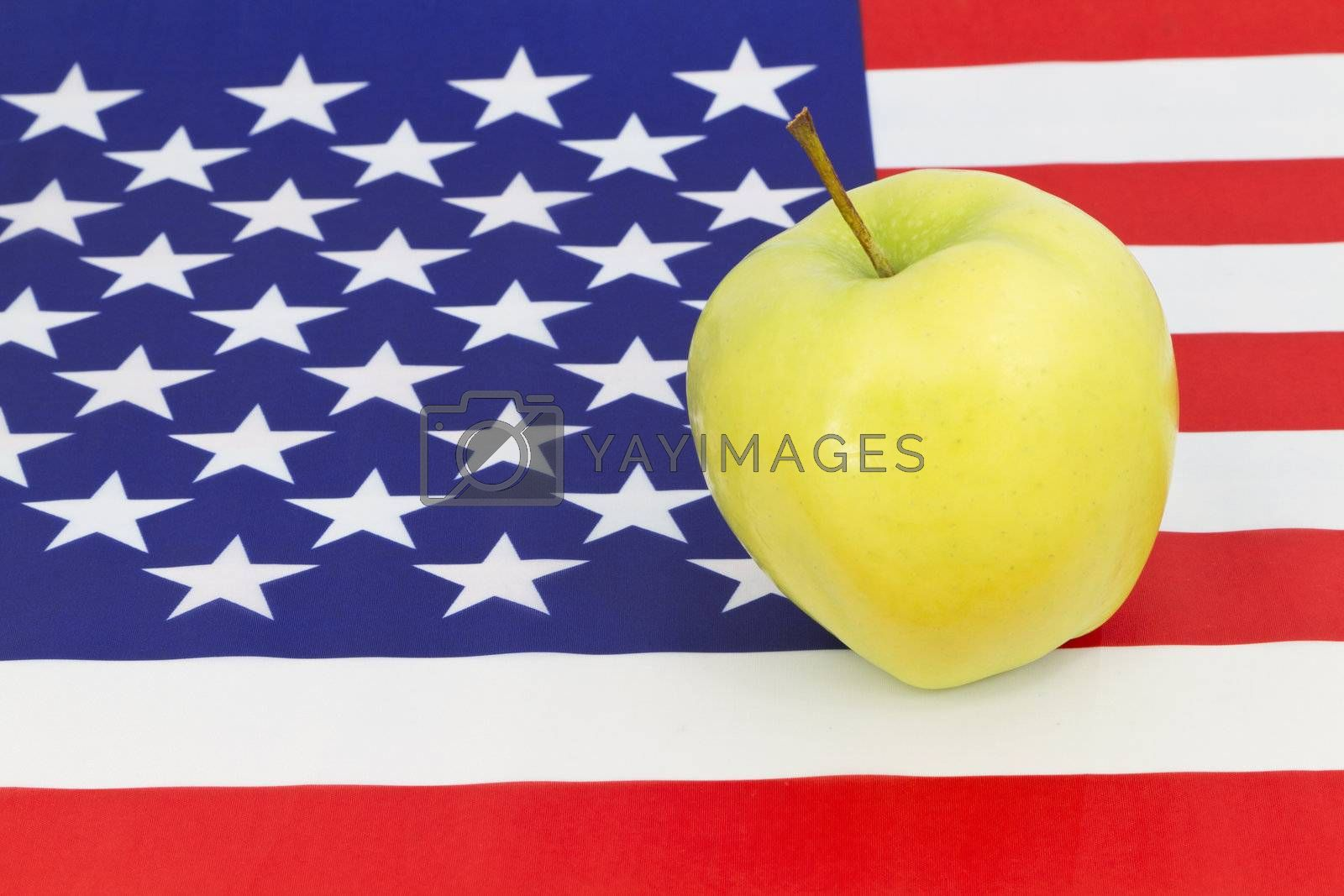 Golden apple, symbol of education, sits on American flag