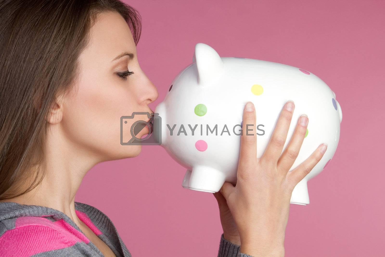 Pretty girl kissing piggy bank