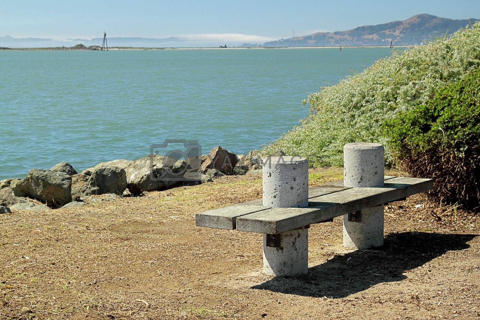 A bench on the seashore on sunny day wiht mountain on background