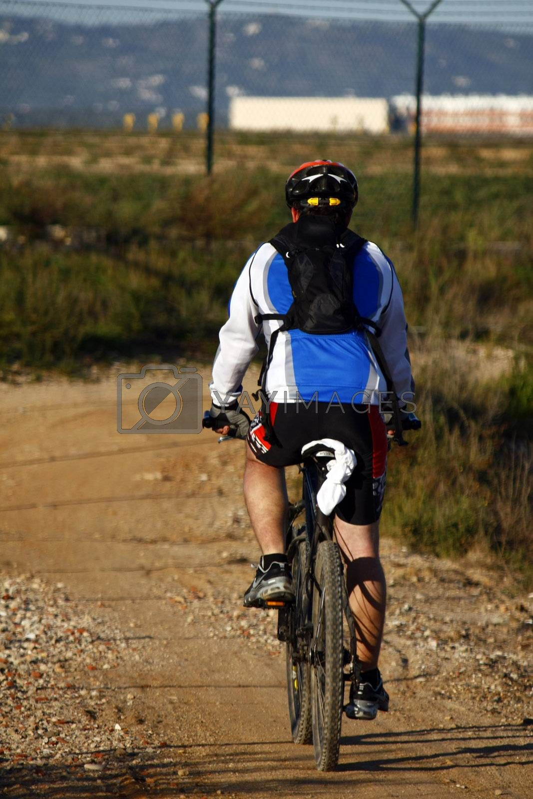 Man wearing sport cloths, riding a bike on the countryside.
