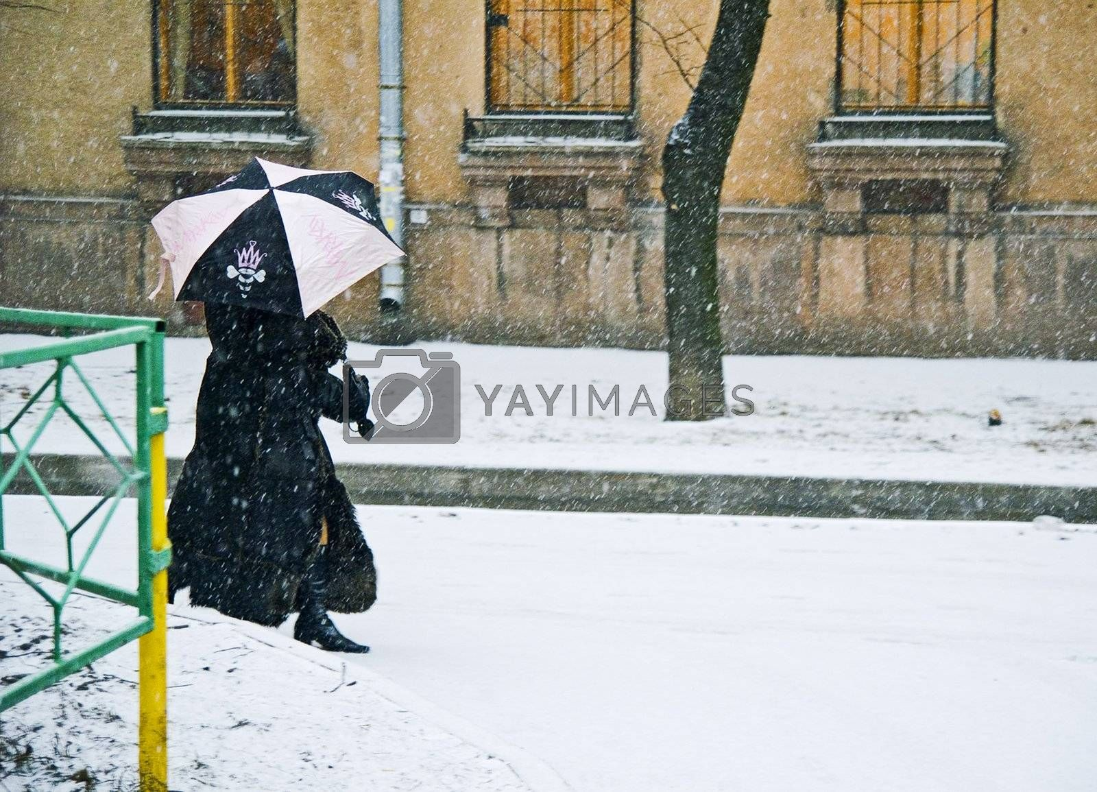 Woman with umbrella in back alley while snowing