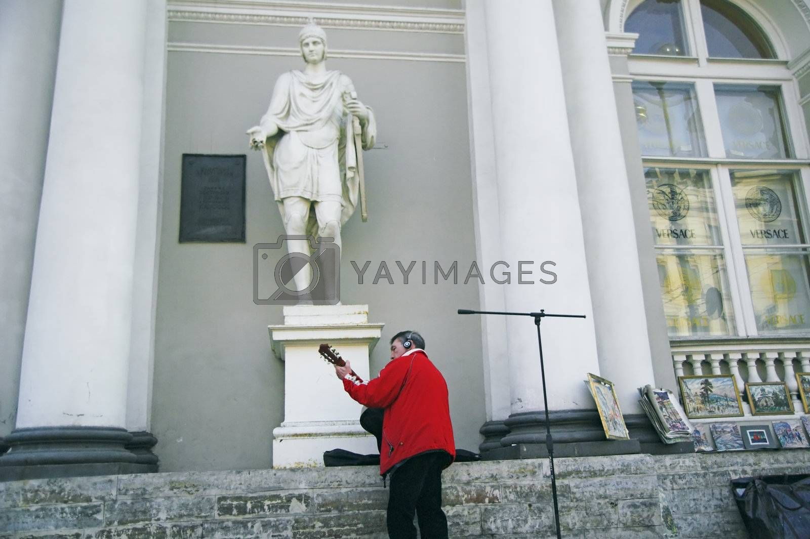 ST PETERSBURG, RUSSIA-MARCH 31, 2008: Street musician playing guitar by sidewalk in front of antique building in Saint Petersburg, Russia