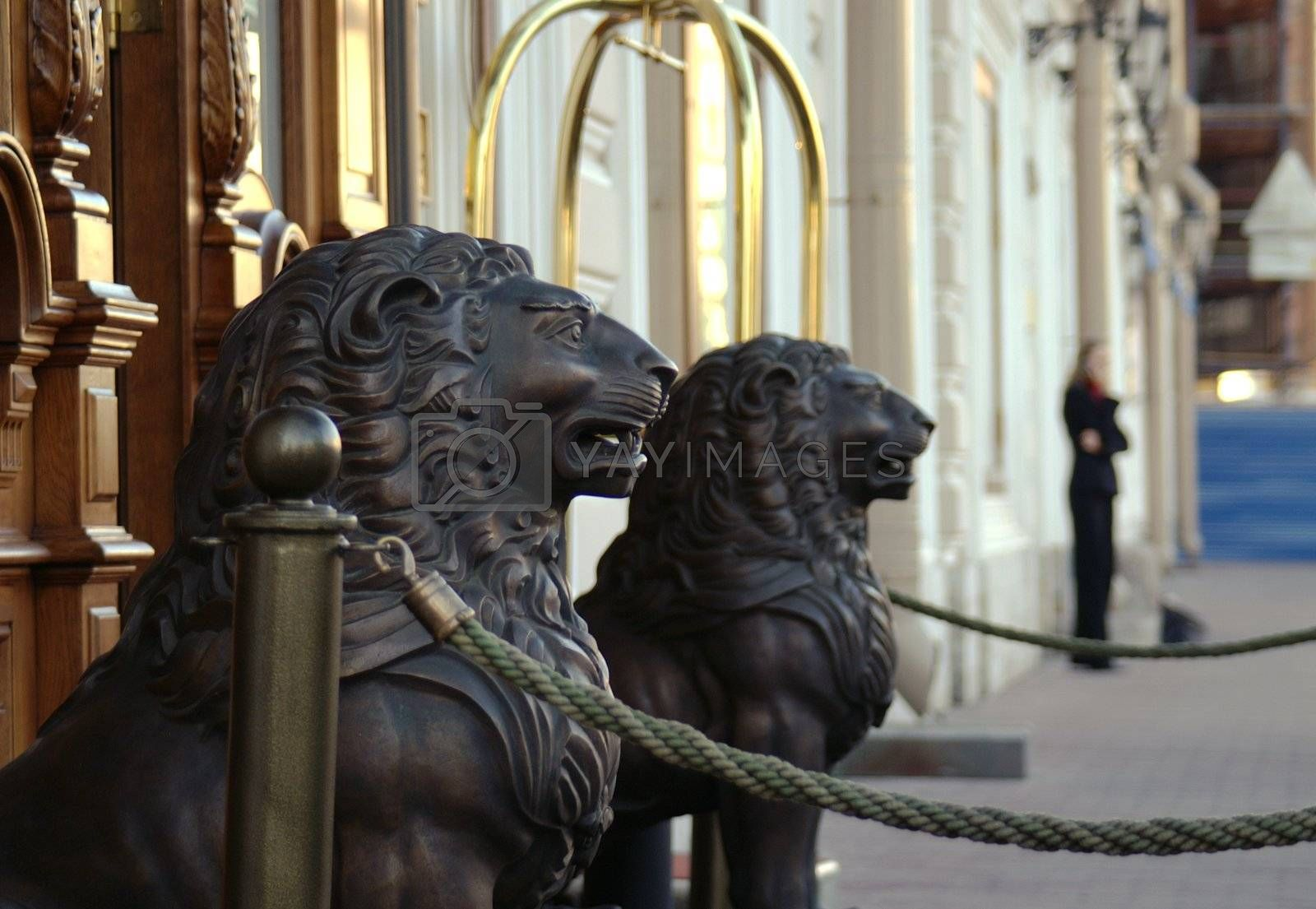 Wooden lion sculptures at the entrance of a hotel.