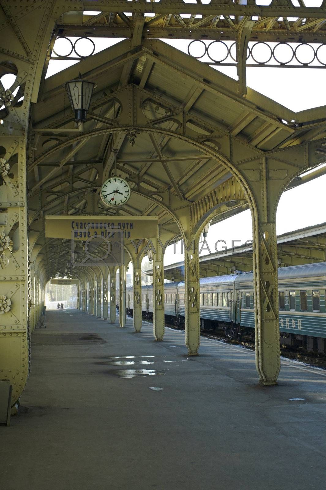 """Railroad station platform with a hanging clock, """"Have a nice trip"""" signboard, and two remote human profiles."""