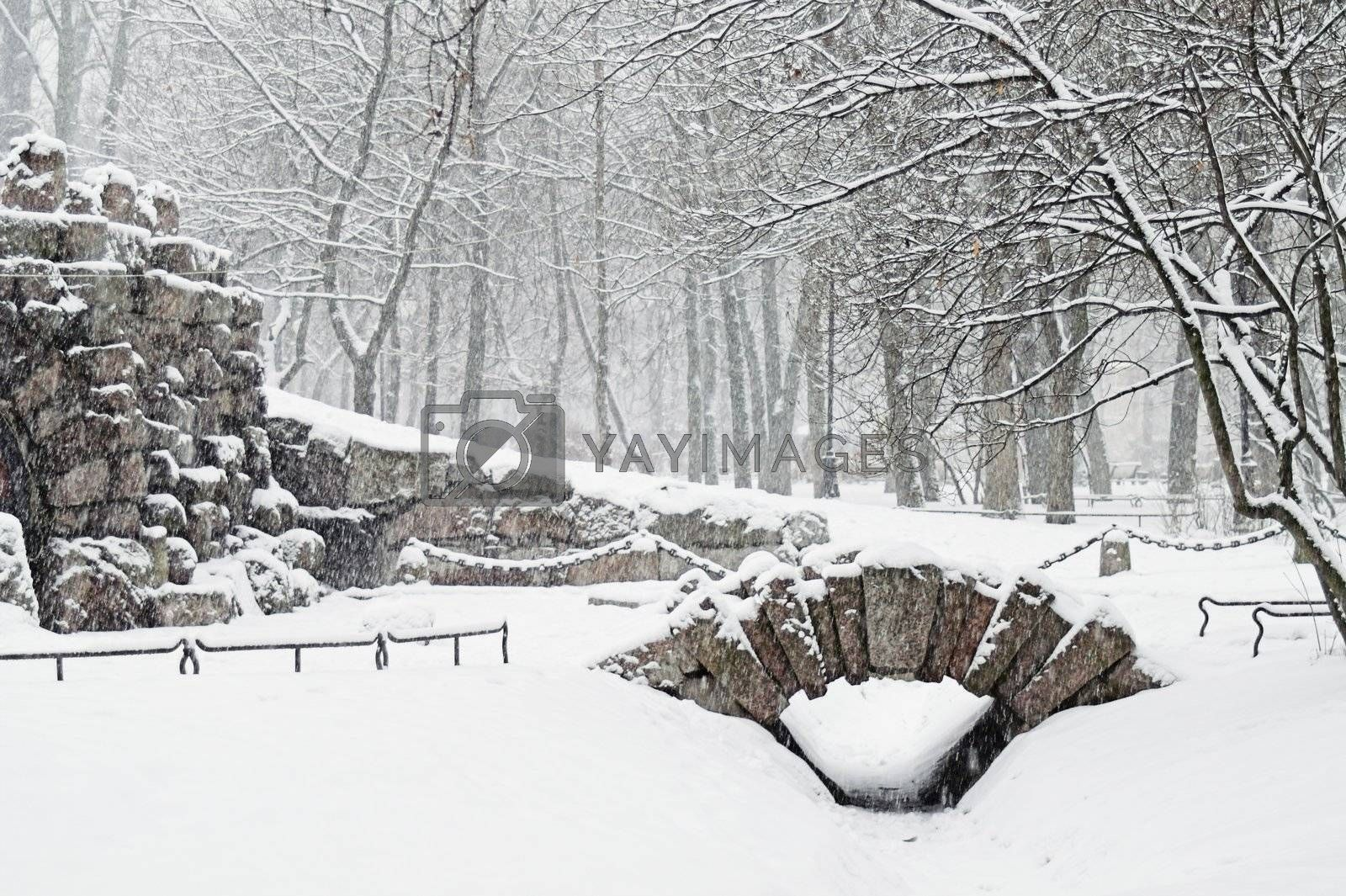 Grotto in city park at snowfall