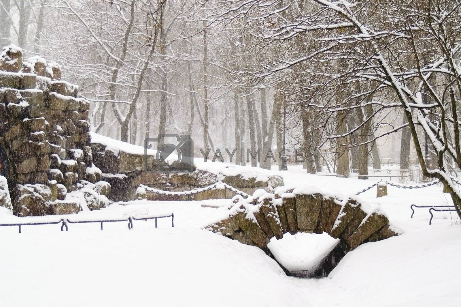 A grotto and a small bridge in a winter park at snowfall.