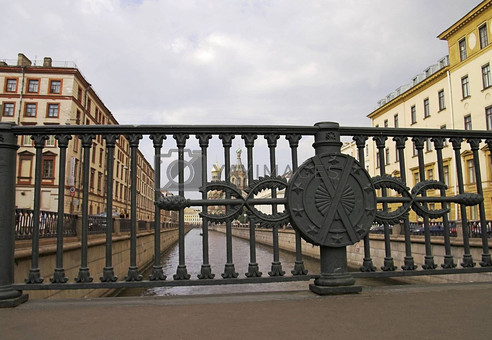 A view from a bridge over Griboyedov\'s Channel in Saint Petersburg, Russia. The Church of the Saviour-on-Blood is seen in the background through the railings.