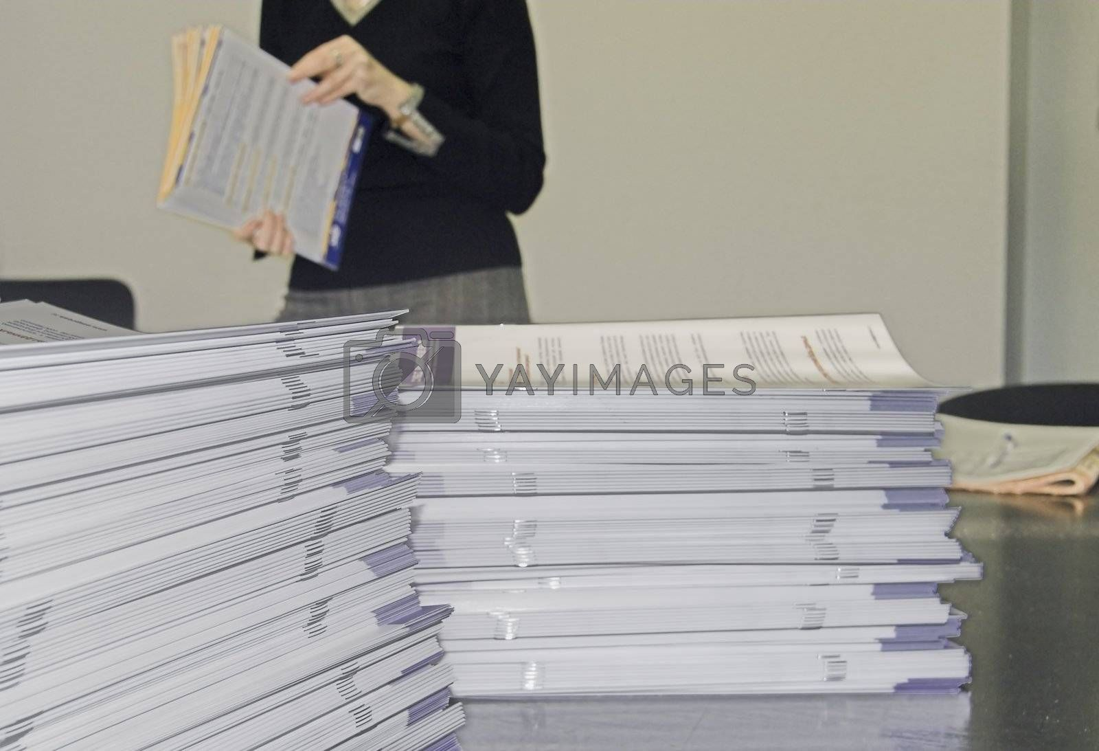 Piles of Handout Pamphlets and Woman in Background