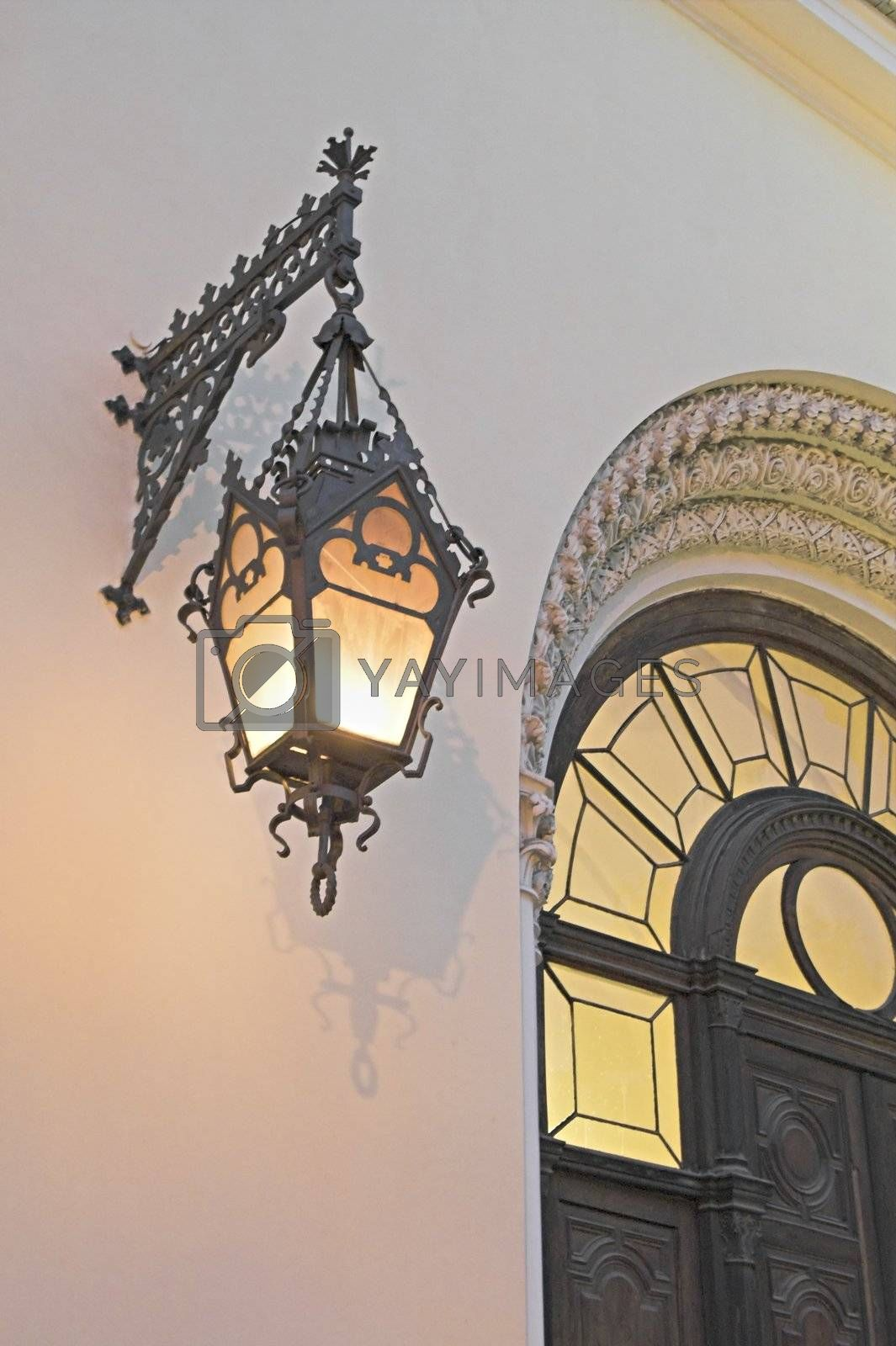 Old lamp on cathedral's wall  by simfan