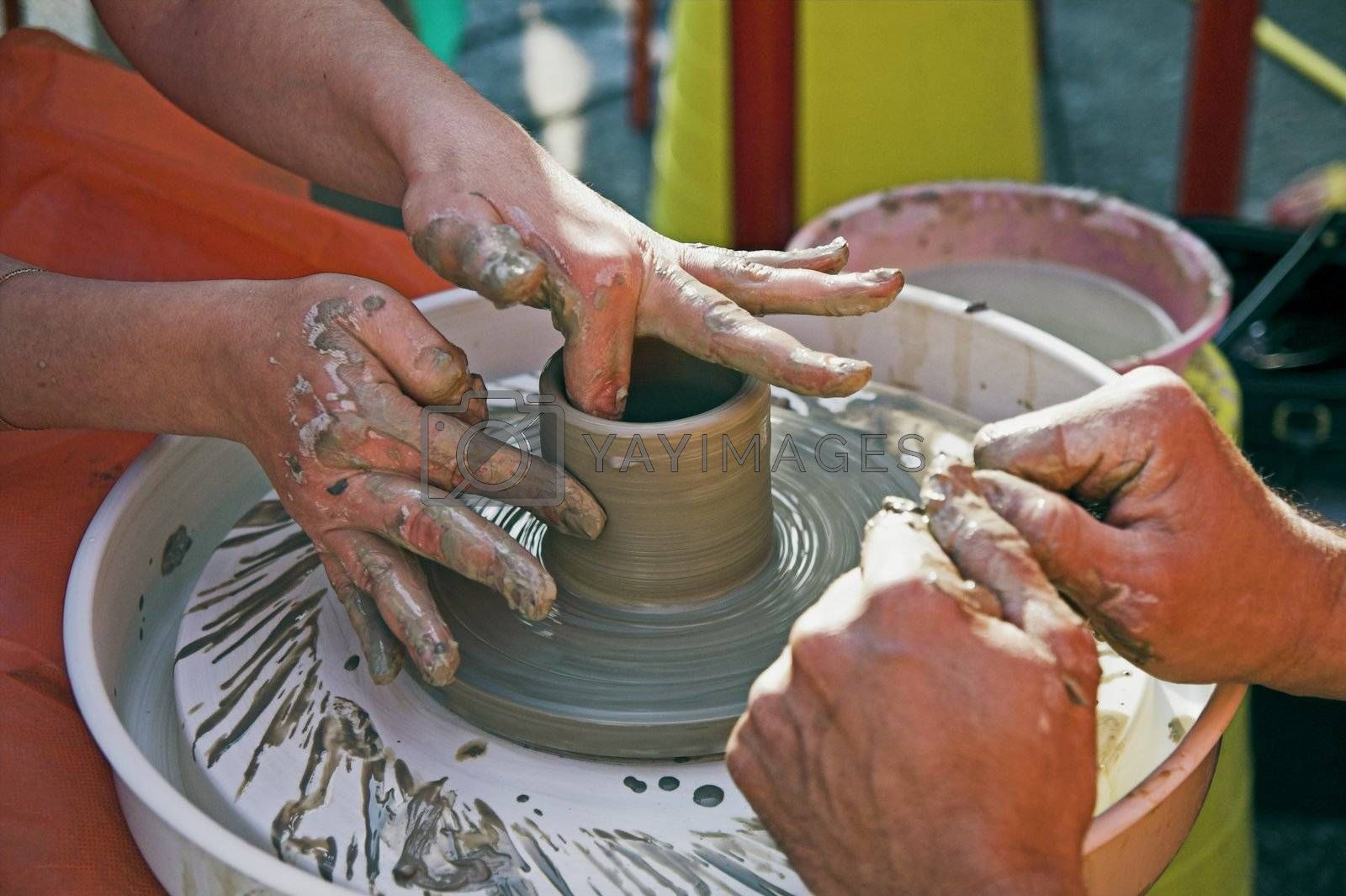 potter's hands guiding woman's hands to help her learn pottery
