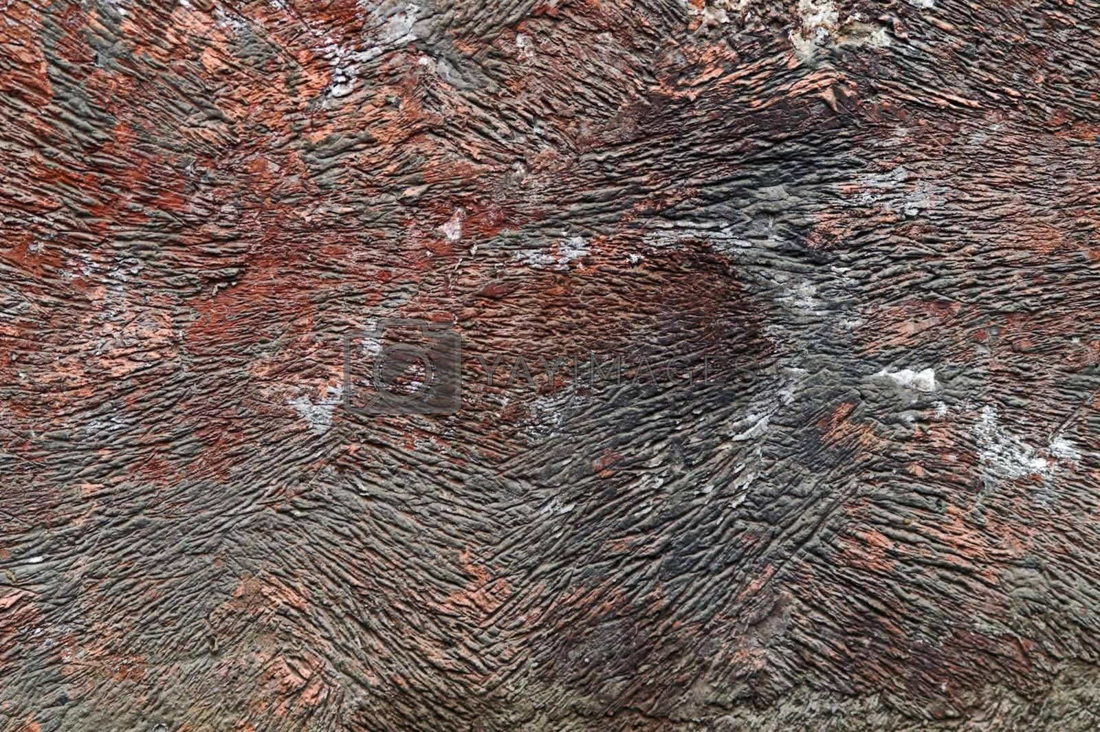 Red-colored corroded wall with surface ridges