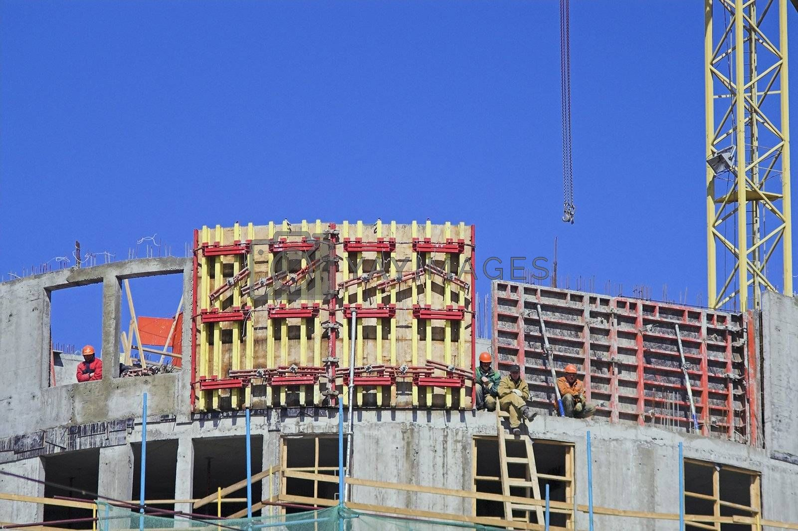 Workers sitting on building structures on construction site