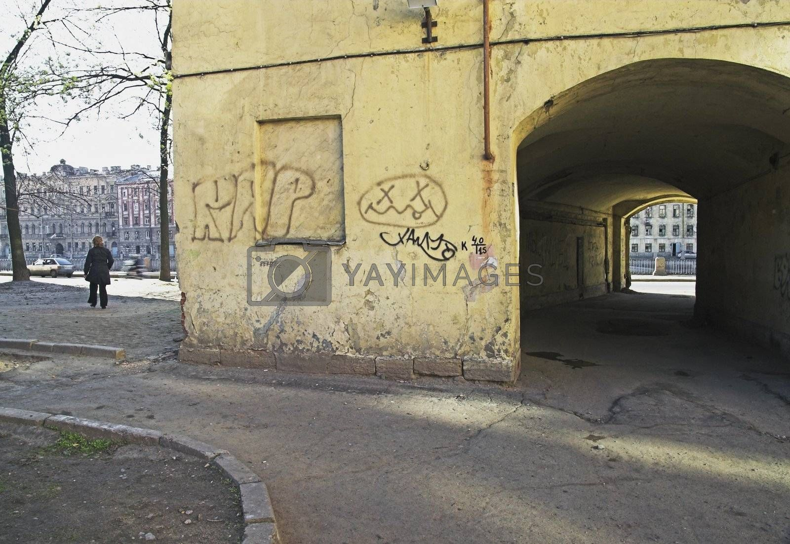 Old building with graffiti and arch in back alley