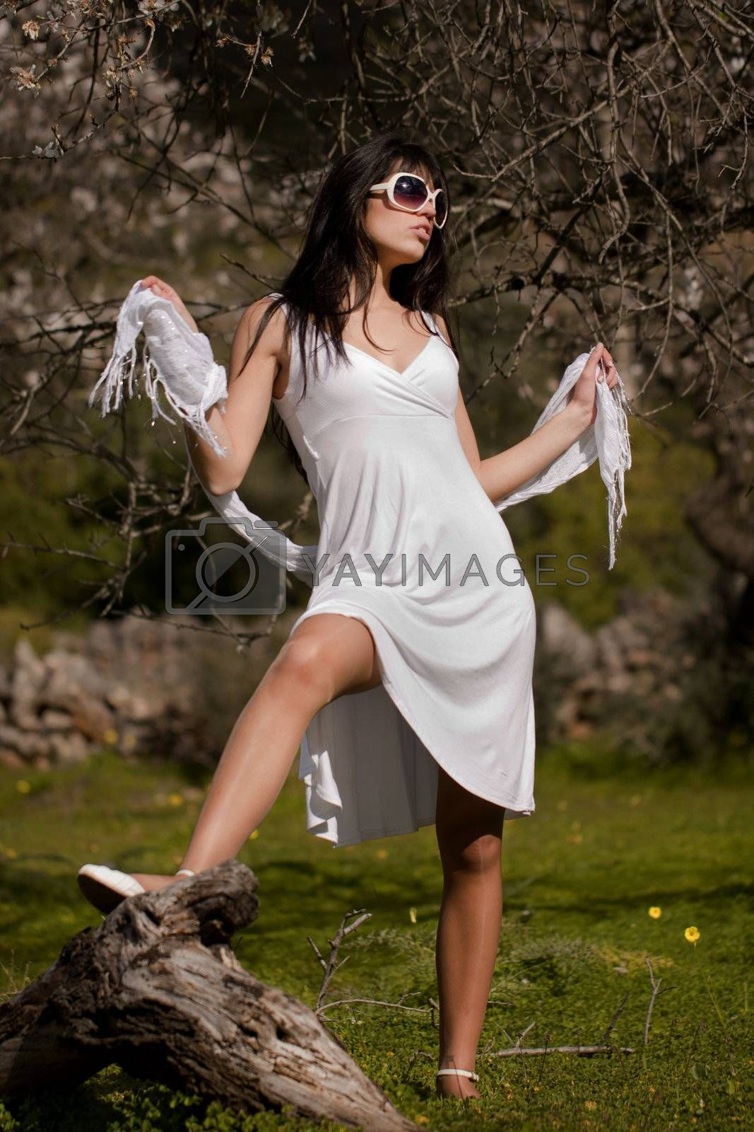 View of a beautiful girl on a white dress on a green grass field next to a almond tree