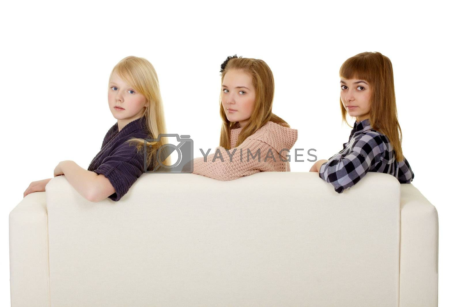 Three young girls - classmate sitting on the couch