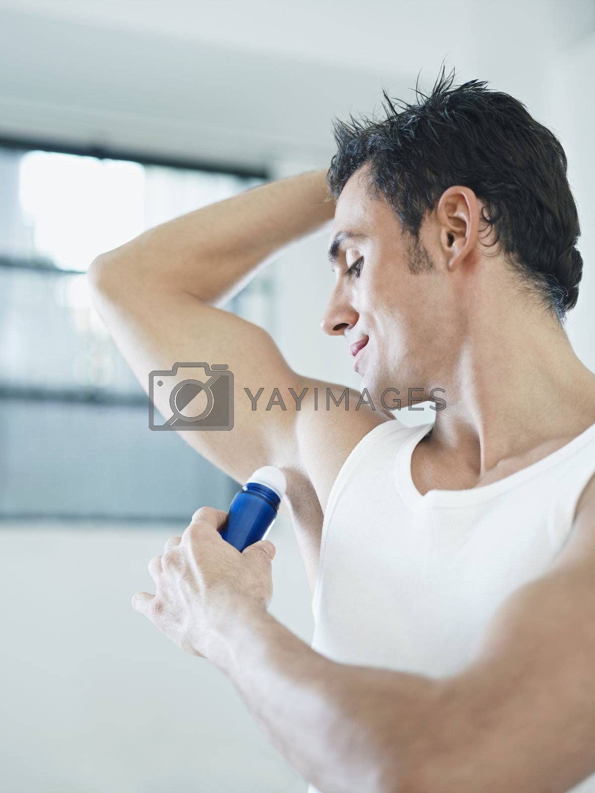 caucasian adult man applying stick deodorant. Vertical shape, waist up, copy space