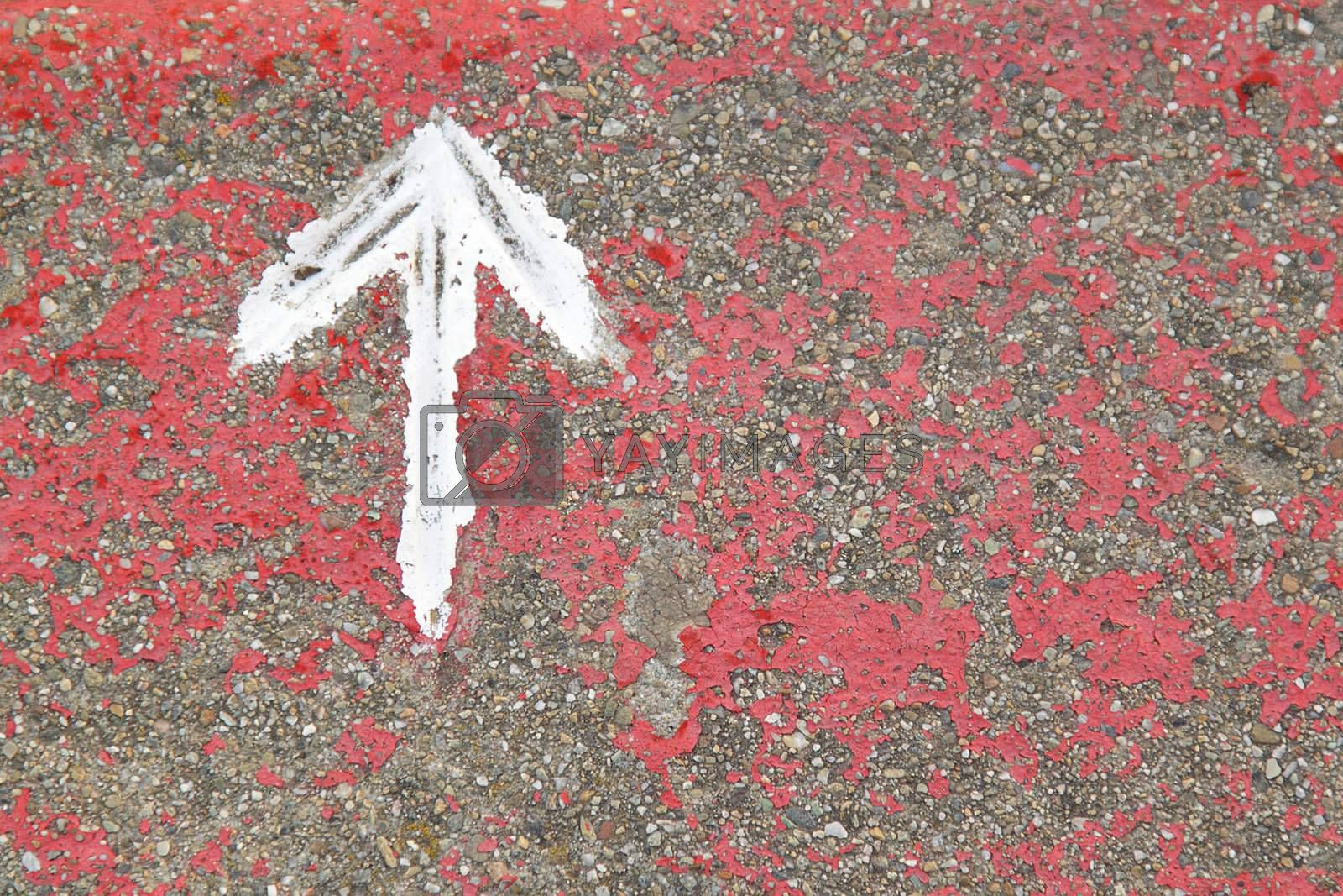 White painted arrow on reddish and gray asphalt