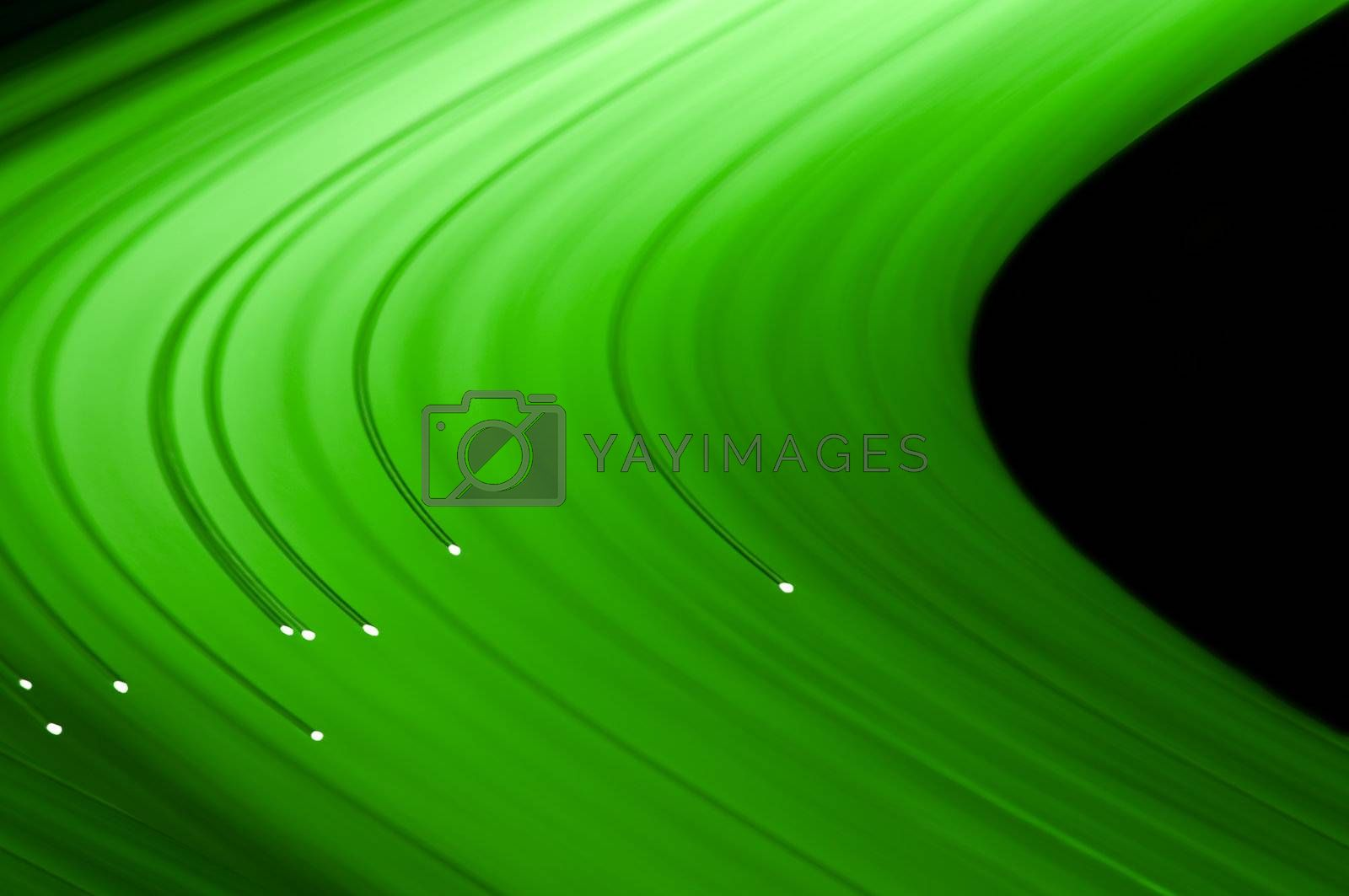 Close up capturing the ends of several illuminated green fibre optic light strands against a black background. Abstract style.
