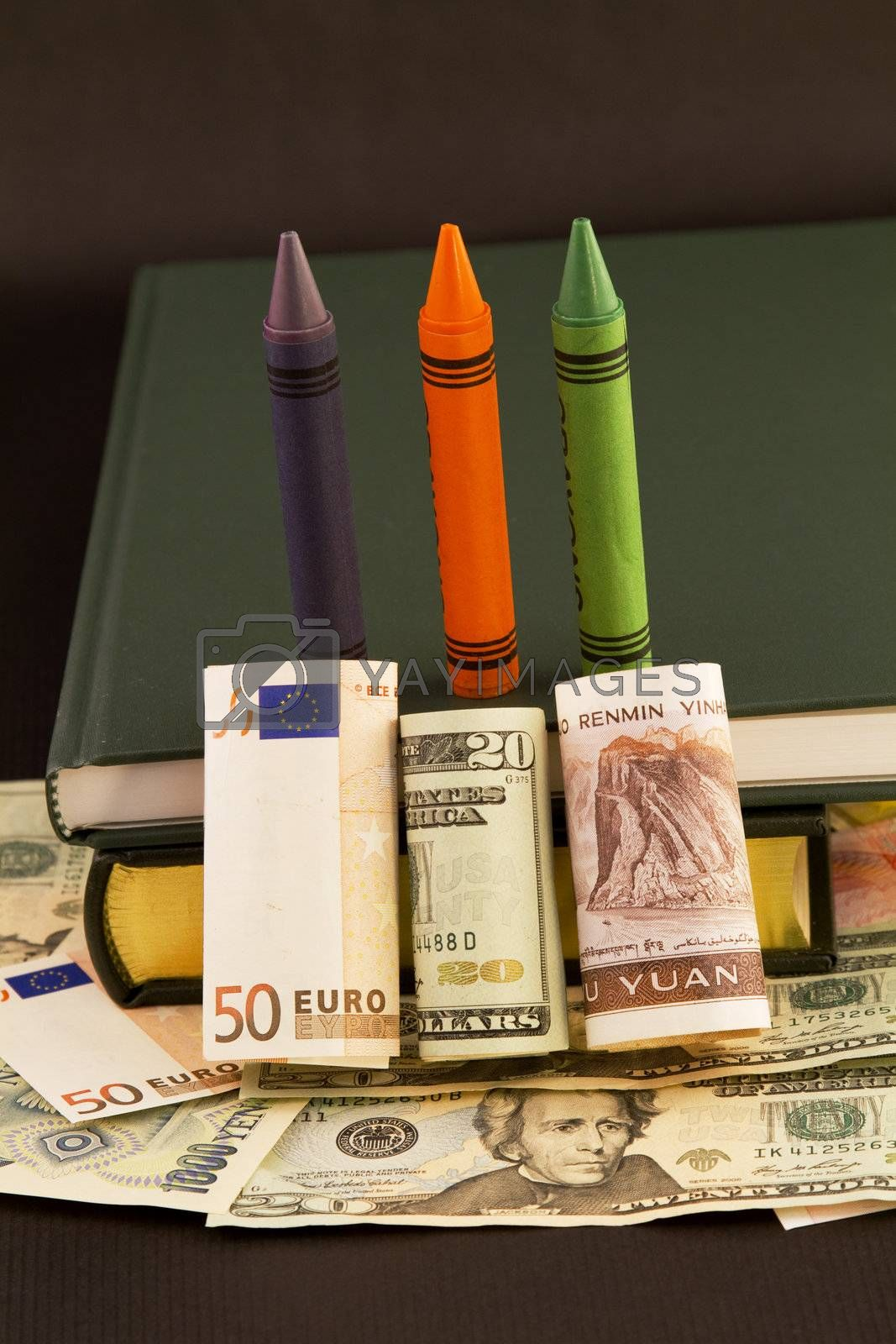 Global emphasis on education symbolized in crayons, books, and multiple currencies, dollar, euro, and yuan