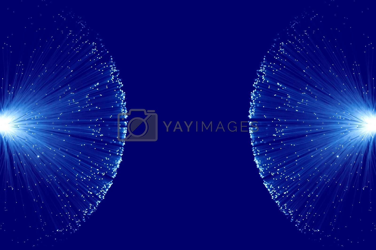 Two groups of illuminated blue fibre optic light strands eminating from the left and right image border against a blue background