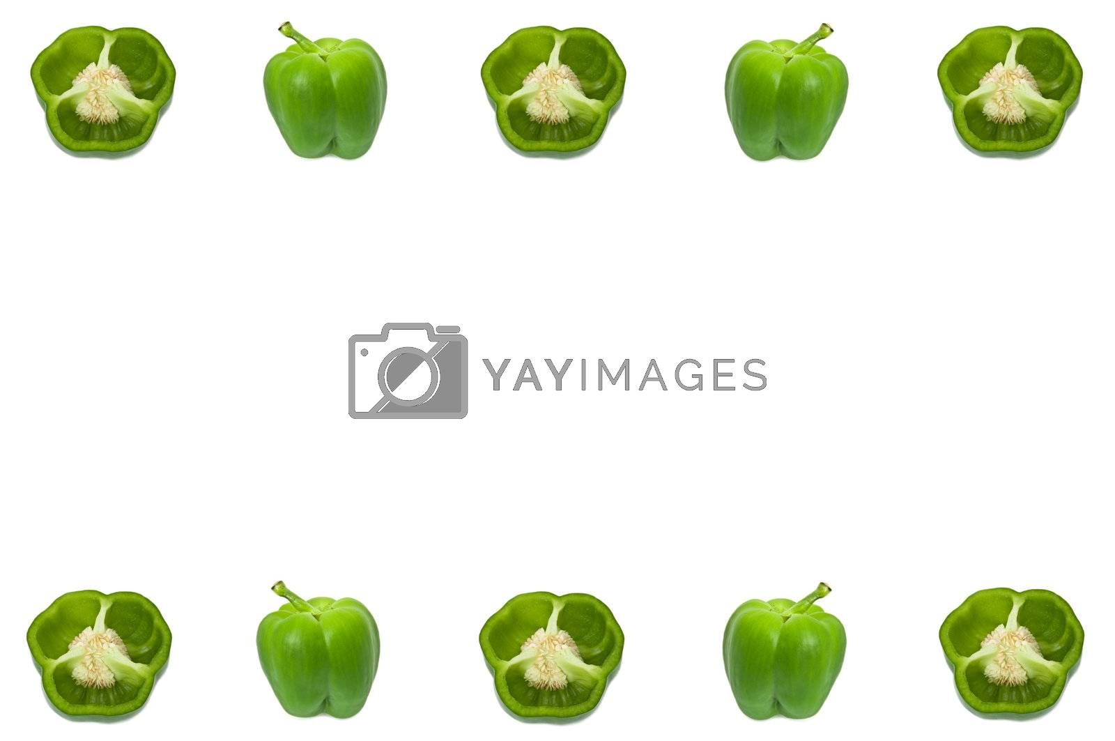 Several small halved and whole green peppers arranged along the border of the image over white.