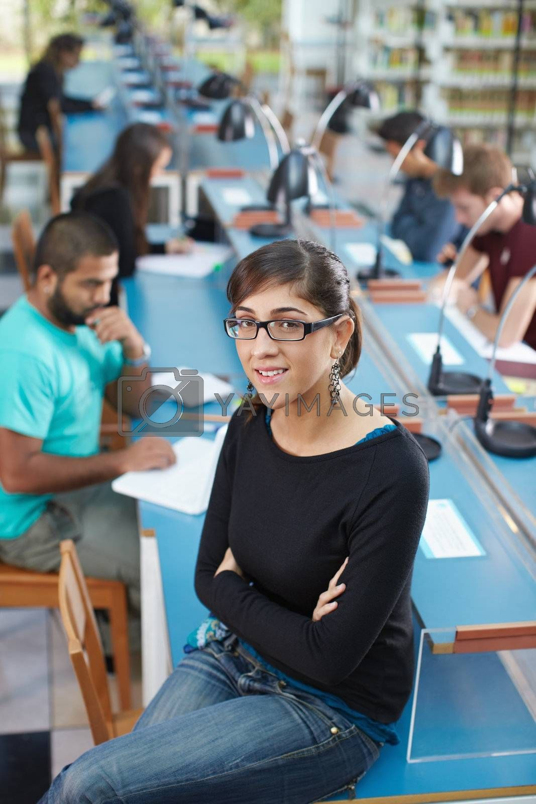 portrait of female college student sitting on table in library and looking at camera. Vertical shape, high angle view
