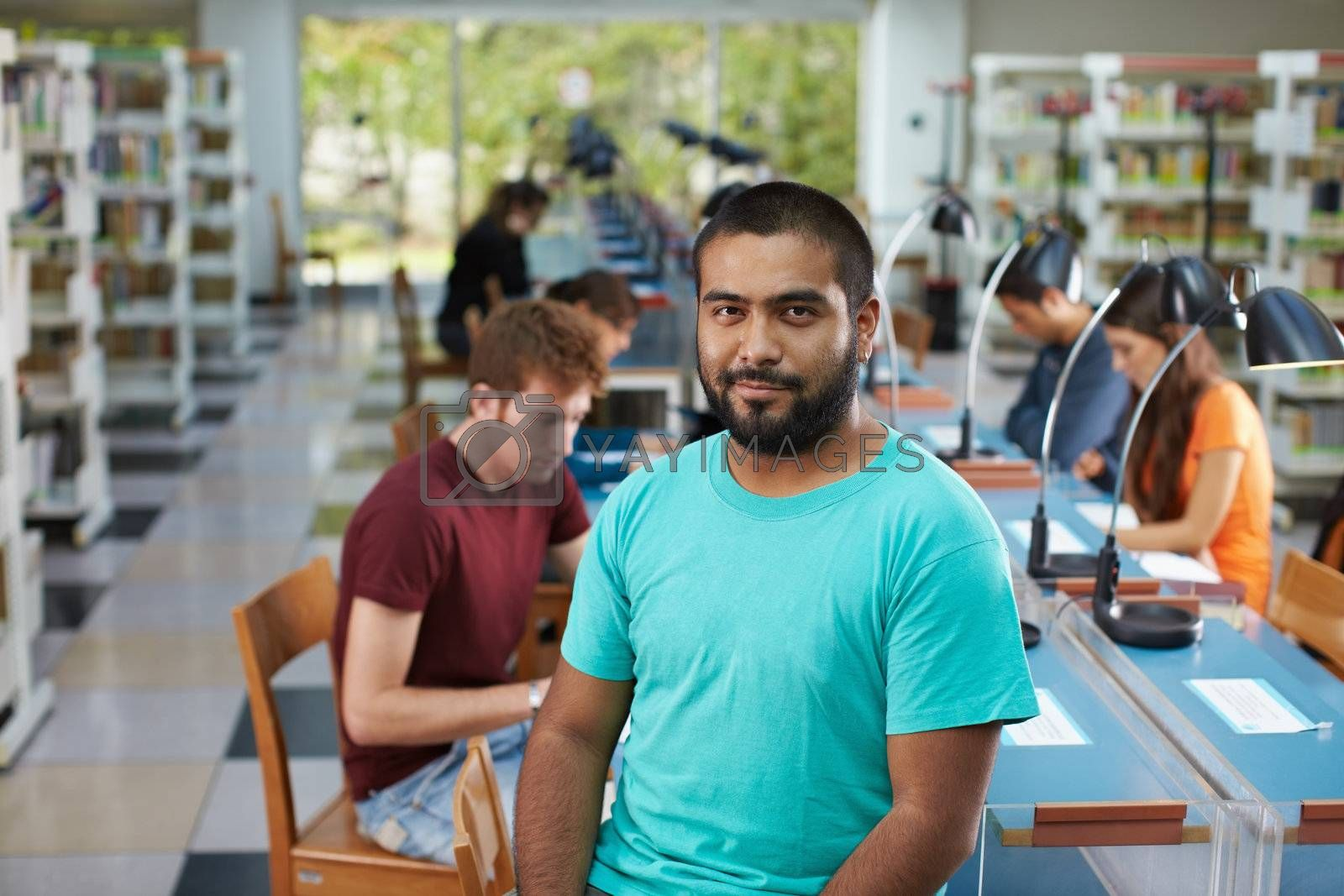portrait of male college student sitting on table in library and looking at camera. Horizontal shape, waist up