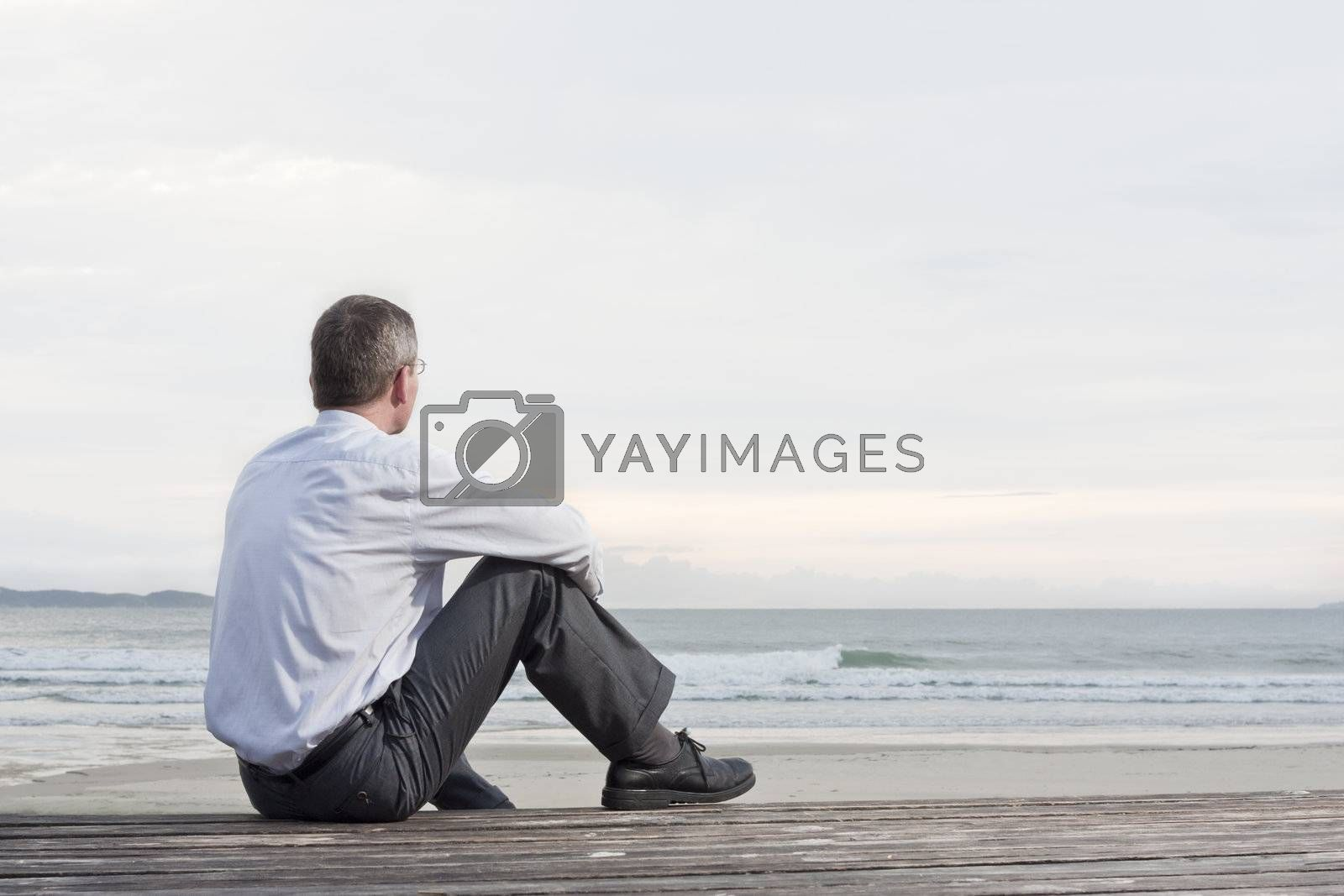 Pensive businessman sitting at the sea by ArtmannWitte