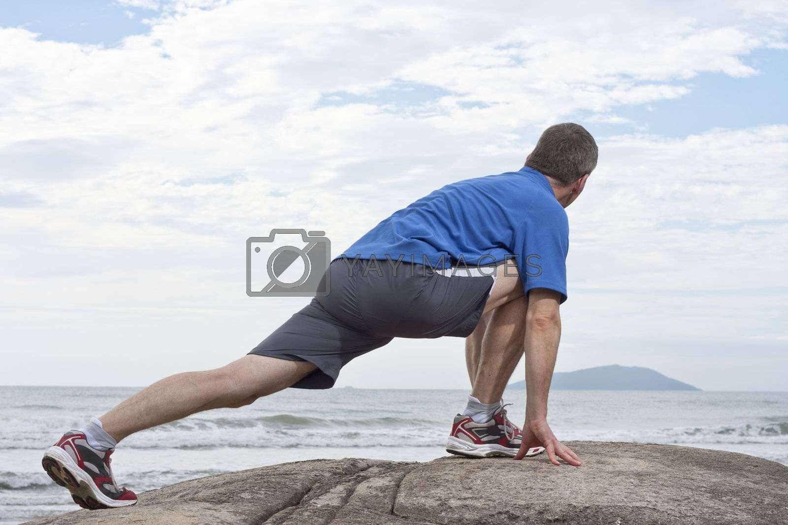 Runner doing stretching exercise by ArtmannWitte
