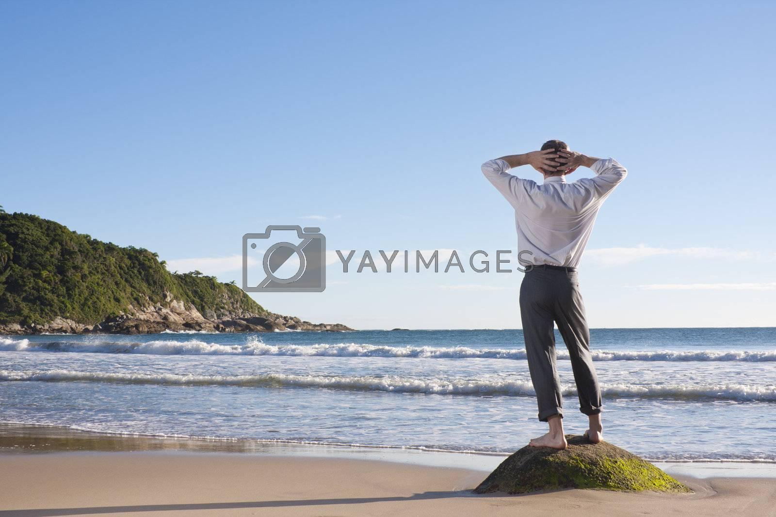 Businessman relaxing on a beach by ArtmannWitte