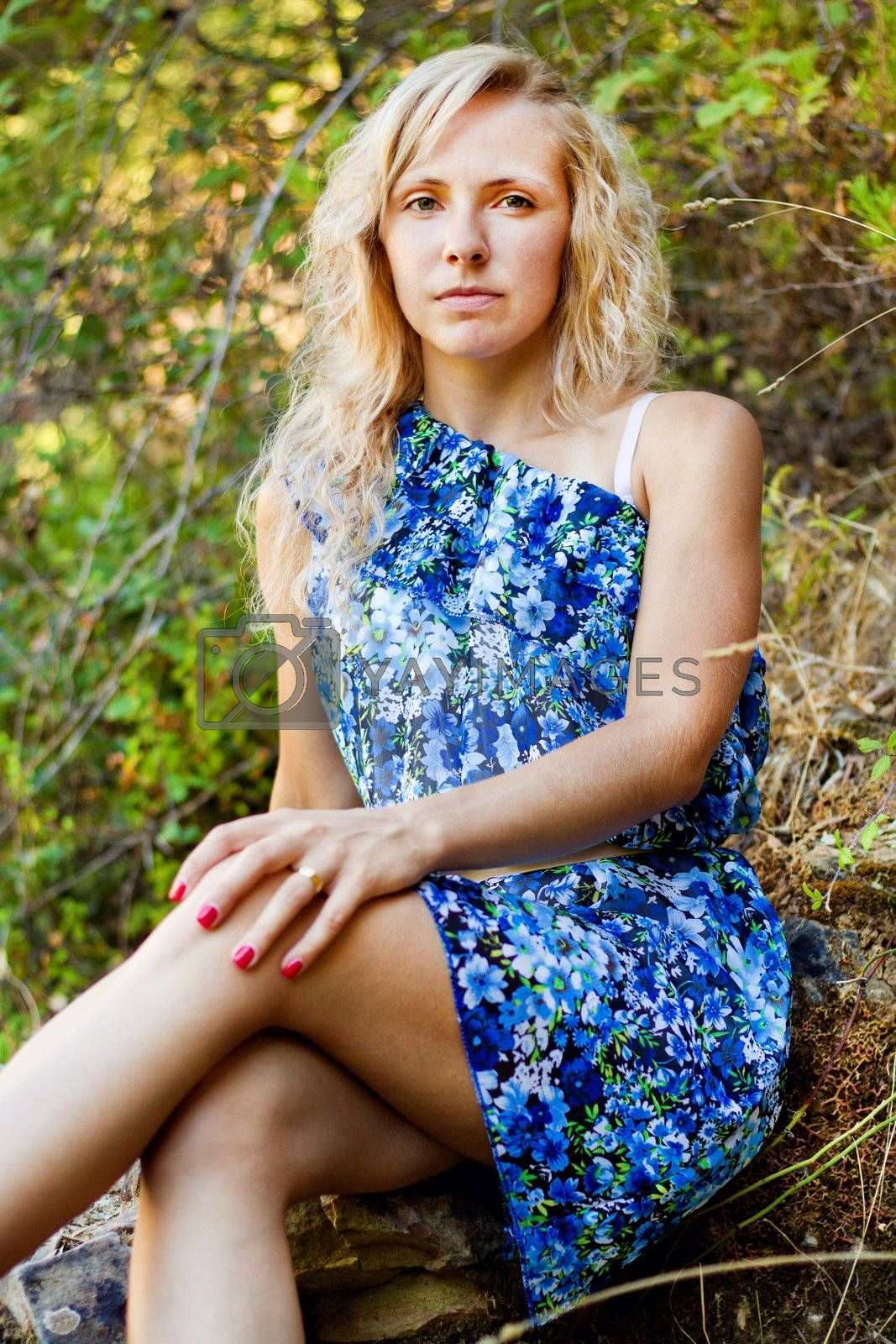 View of a beautiful young girl with a blue dress on the forest.