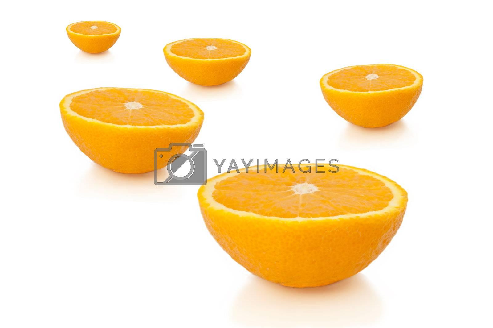 FIve freshly cut orange halves arranged over white.