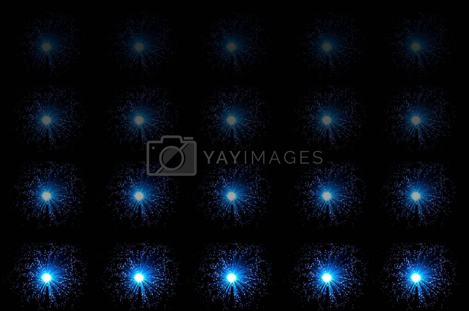 Twenty small illuminated blue fibre optic lamps in horizontal line formations with each line fading progressively towards the top of the image. Black background.
