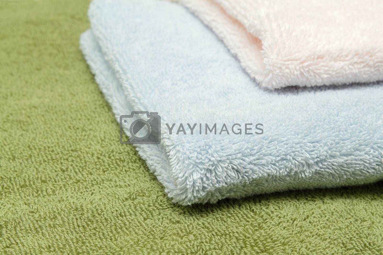 A stack of three bath towels of different colors