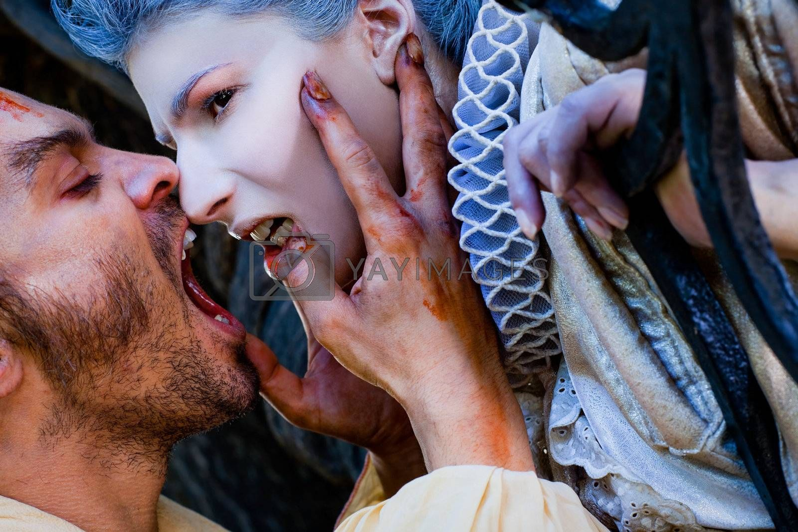 Close-up of male vampire with wounds biting woman in medieval dress