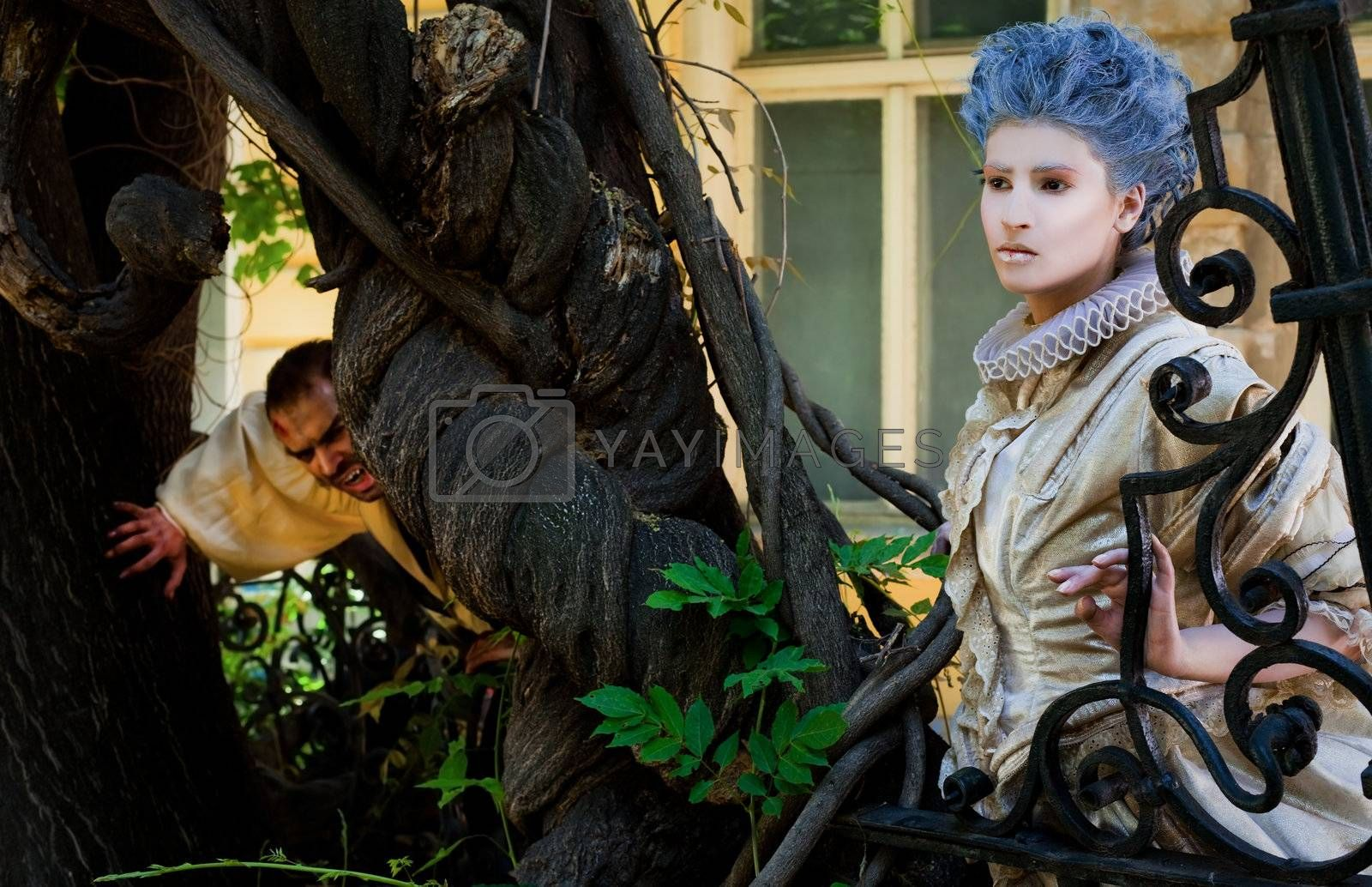 Male vampire stalking woman dressed in medieval costume