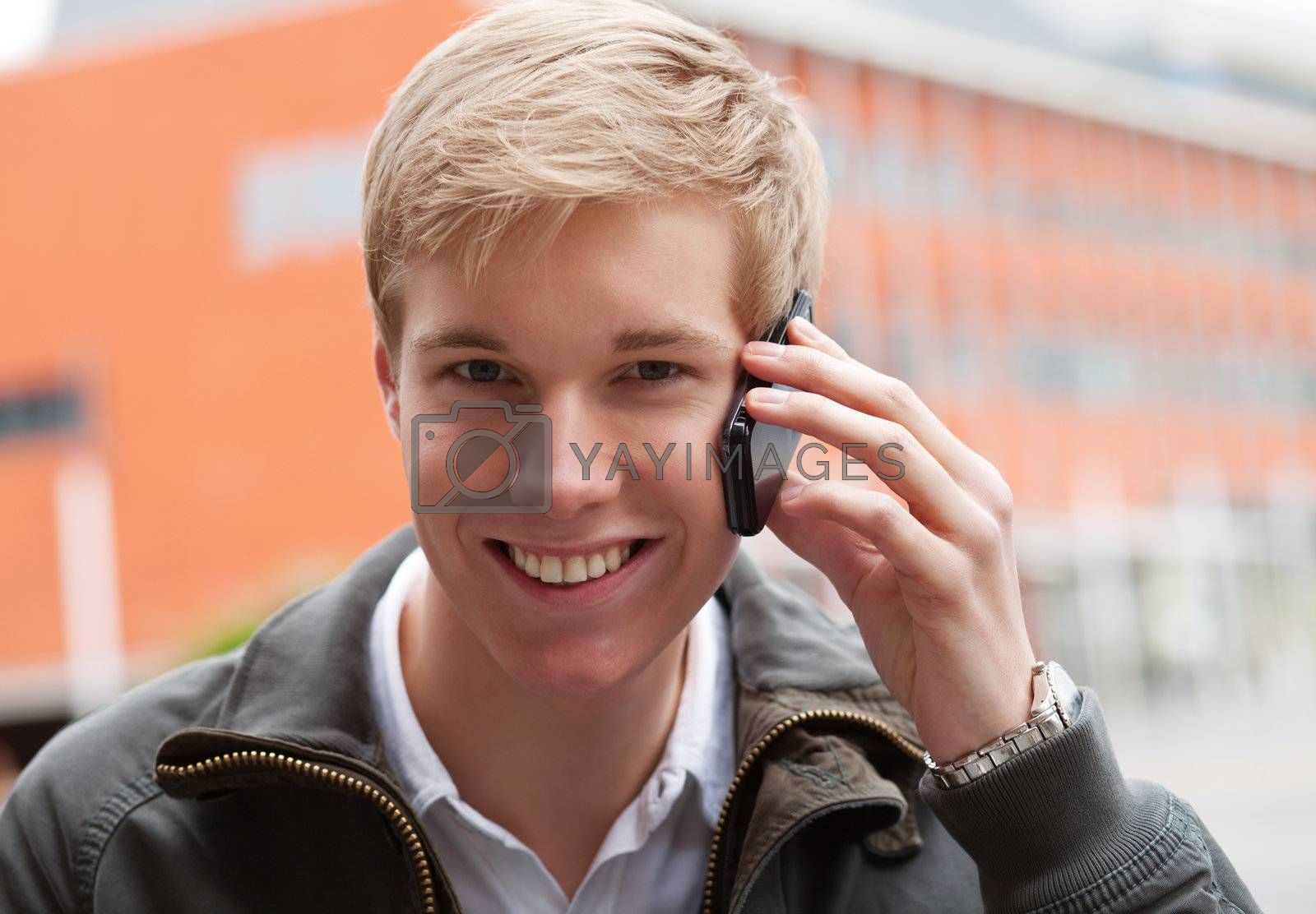 Young blond handsome smiling guy with mobile phone